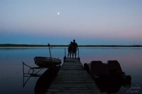 A couple standing out on a dock in the evening