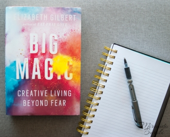 A copy of Big Magic, by Elizabeth Gilbert, beside a notebook and pen
