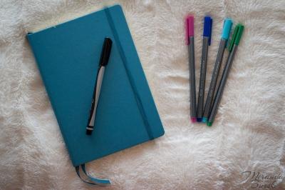 A blue bullet journal with assorted markers
