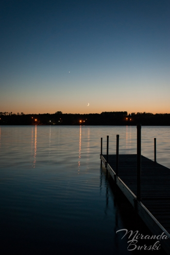 A dock on a peaceful lake at twilight