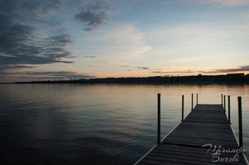 A dock on a lake at sunset