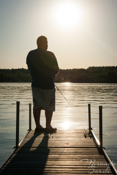 A man fishing off of a dock in the late afternoon