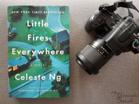 A copy of Little Fires Everywhere, by Celeste Ng, beside a camera