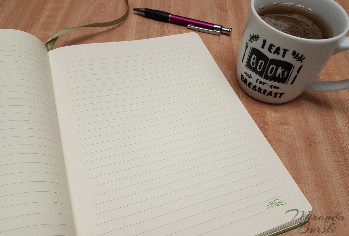 An open notebook, pen, and cup of tea