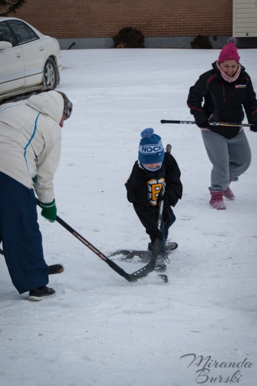 A young kid and two adults playing street hockey