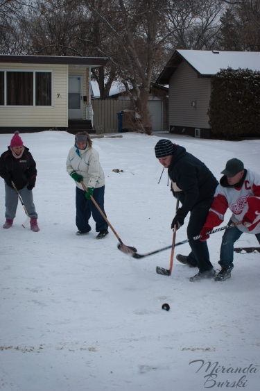 Four people circling a hockey puck