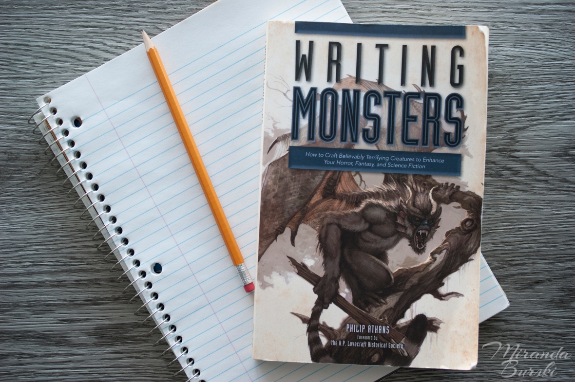 A copy of Writing Monsters, by Philip Athans, on top of a notebook and pencil