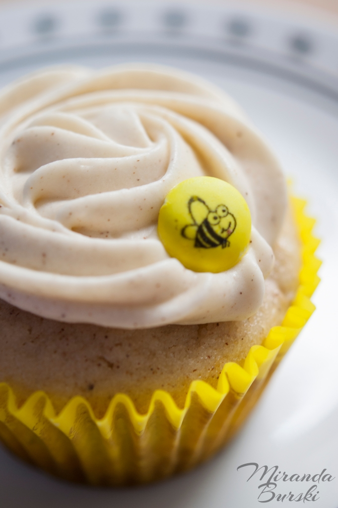 An Apple Pie cupcake with a yellow liner and an M&M with a bumble-bee on it.