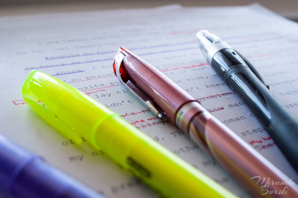 A pencil, red pen, yellow highlighter, and blue highlighter lying on marked-up text.