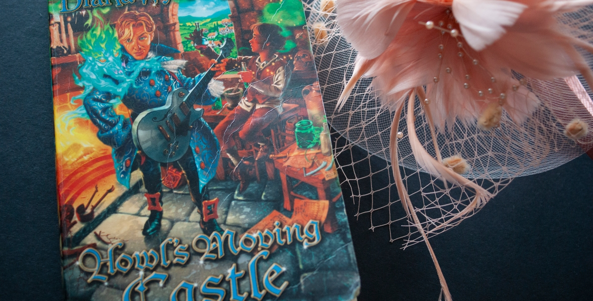 A copy of Howl's Moving Castle, by Diana Wynne Jones, alongside a pink hat.