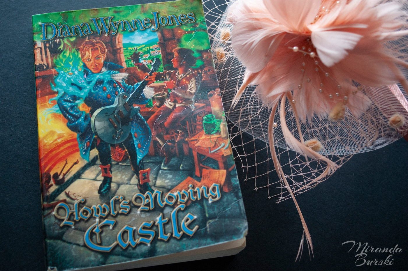 A copy of Howl's Moving Castle, by Diana Wynne Jones, alongside a pink hat.