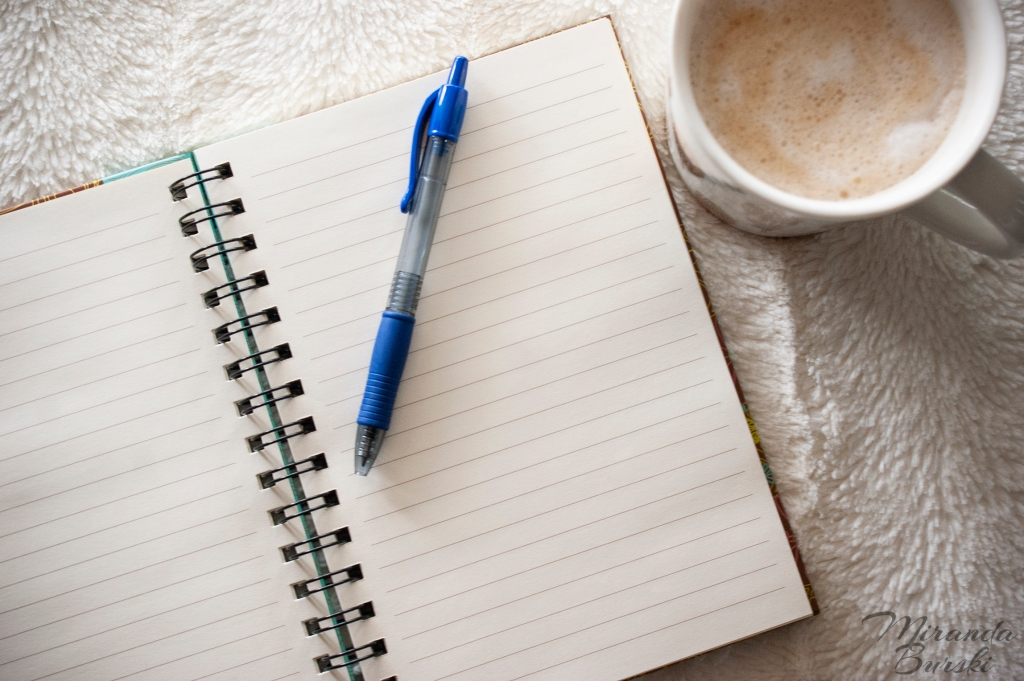 A pen sitting on top of a blank notebook page, with a cafe-mocha beside it.