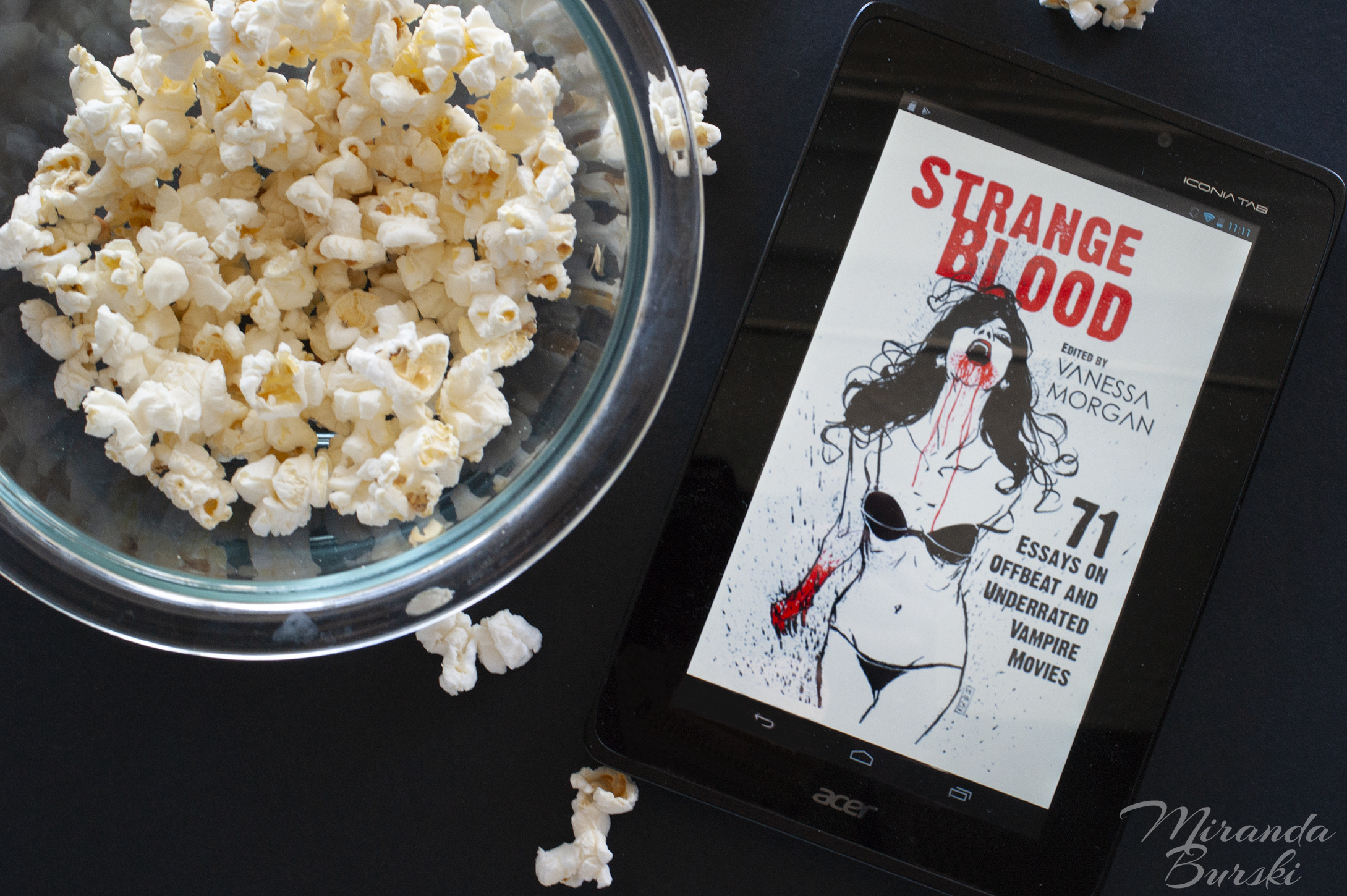 An e-book copy of Strange Blood, edited by Vanessa Morgan, beside a bowl of popcorn.