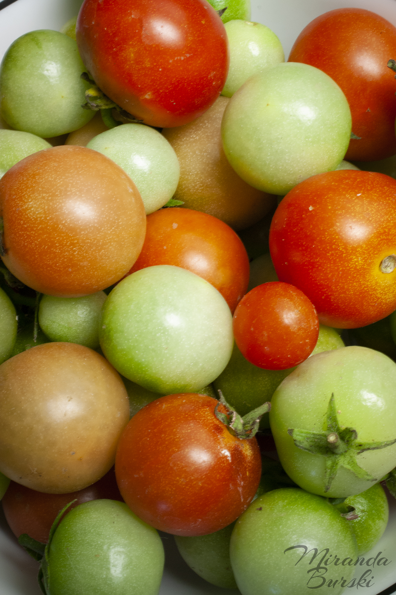 A bowl of green, orange and red cherry tomatoes.