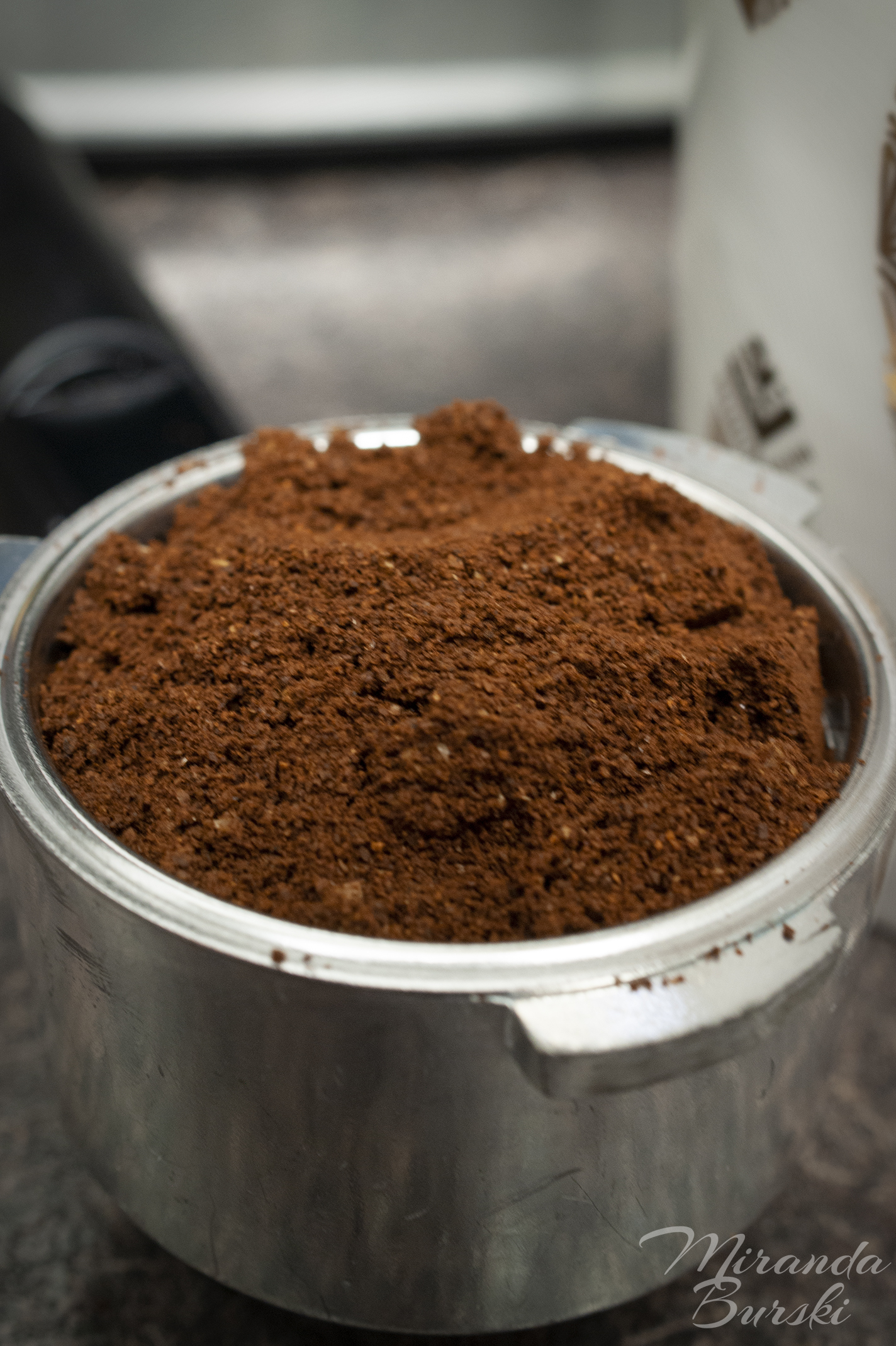 An espresso cup filled with ground coffee beans.