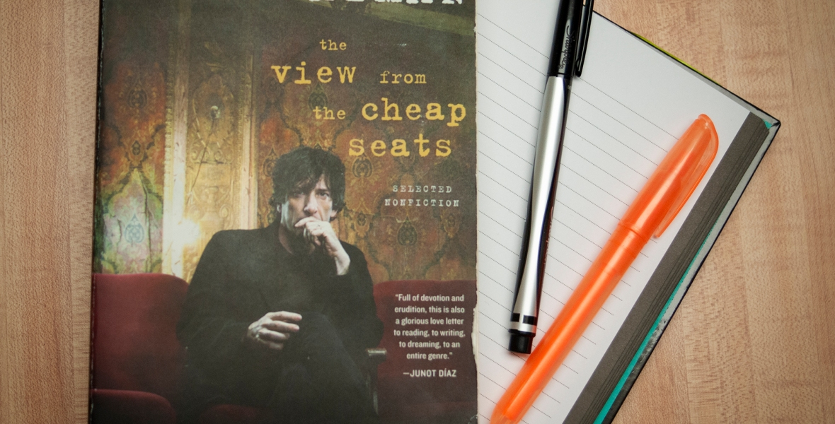 A copy of The View from the Cheap Seats, by Neil Gaiman, alongside a notebook, marker and highlighter.