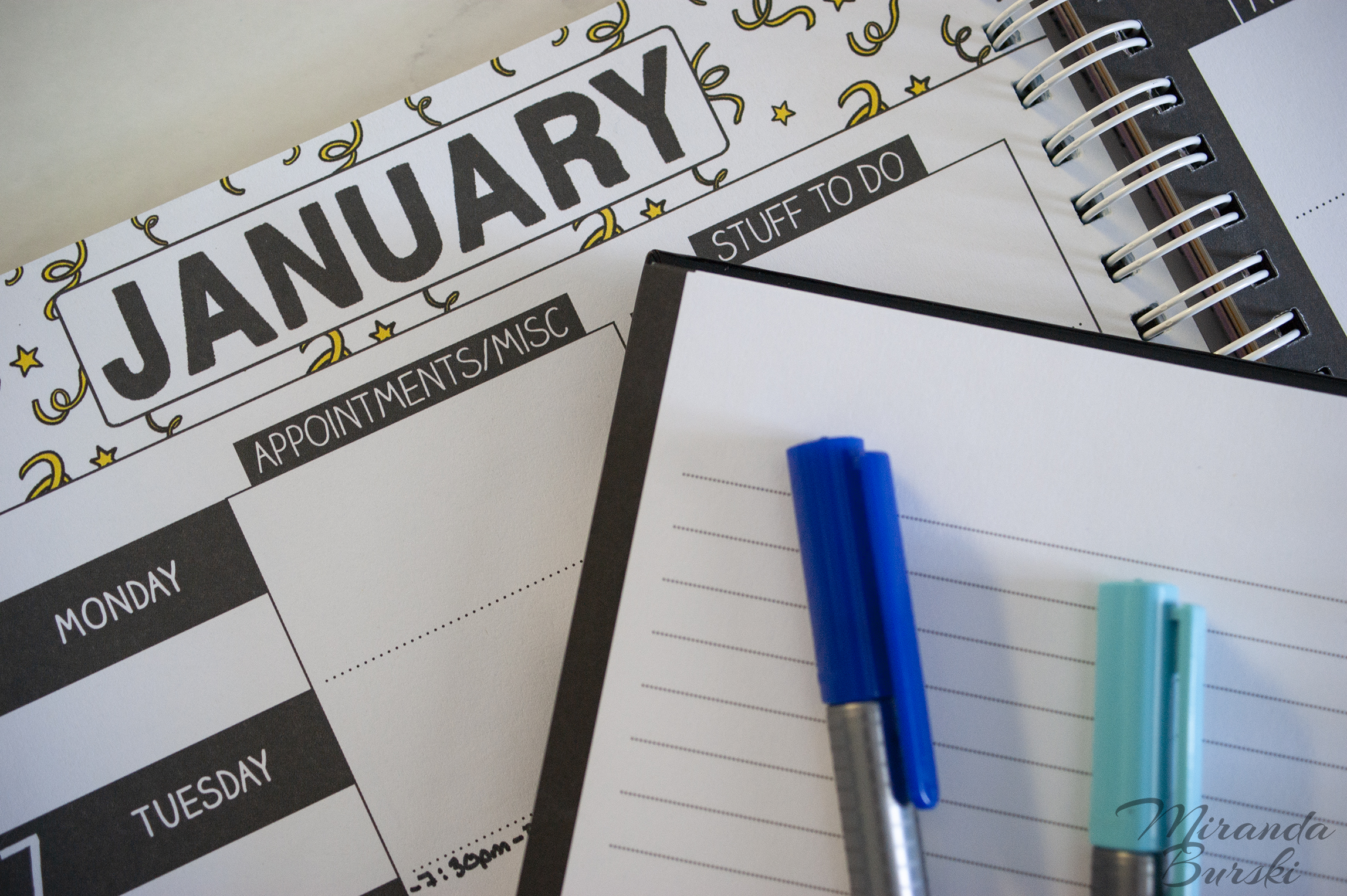 Blue markers on top of an empty notebook and January weekly planner.