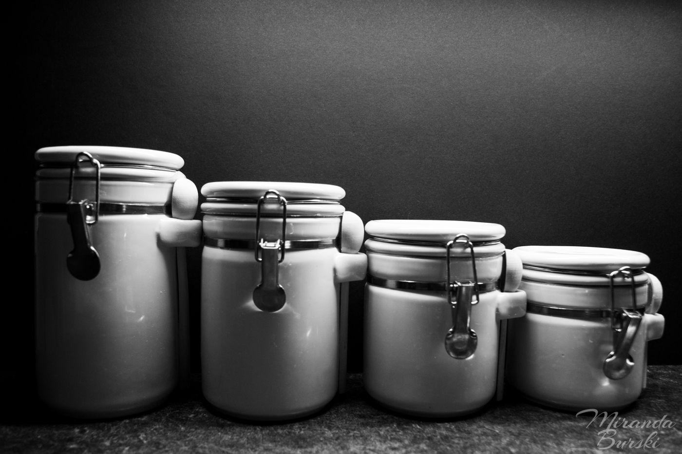 A black and white photo of four white canisters.
