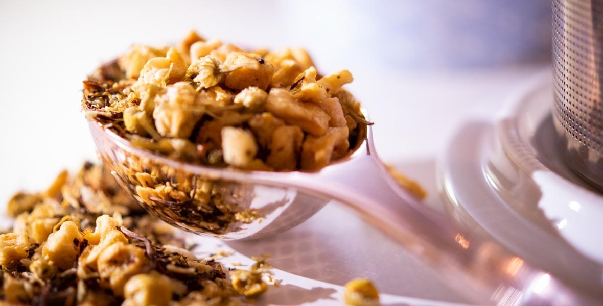 A close-up of a spoonful of loose-leaf tea.