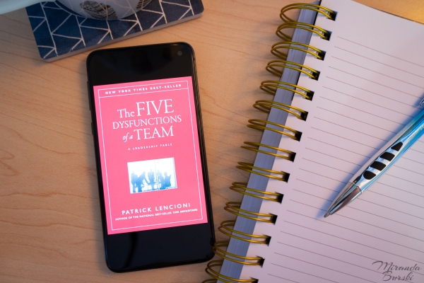 A digital copy of the cover of The Five Dysfunctions of a Team, by Patrick Lencioni, beside a notebook, pen and coffee mug.