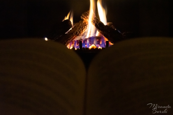 A book open in front of a lit fire.