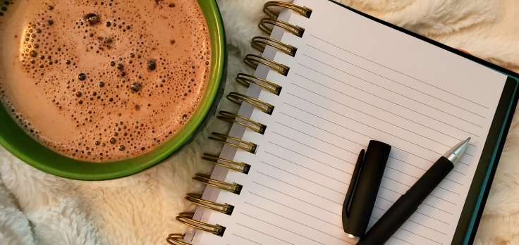 A cup of hot chocolate beside a notebook and pen