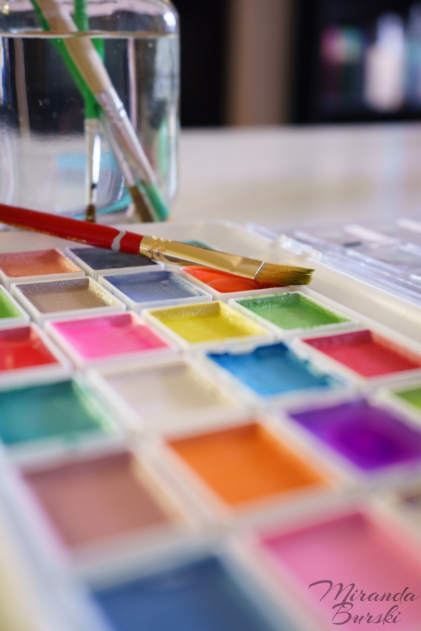 A paint brush sitting on a watercolour palette, with more brushes and water in the background.