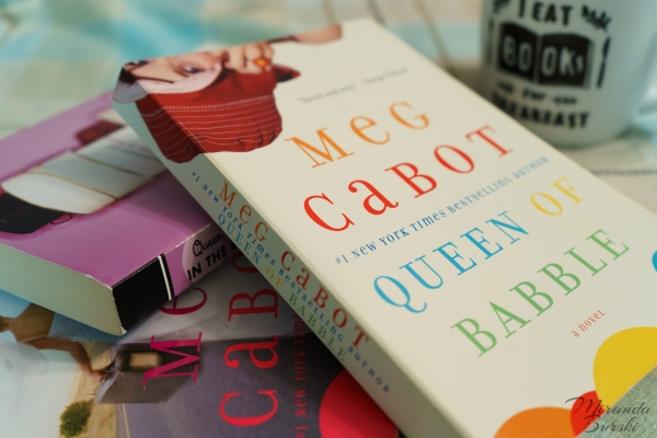 The Queen of Babble book series, by Meg Cabot, beside a coffee mug.