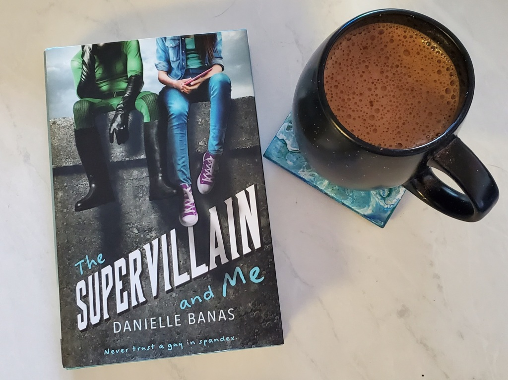 The cover of The Supervillain and Me, by Danielle Banas, beside a cup of coffee.